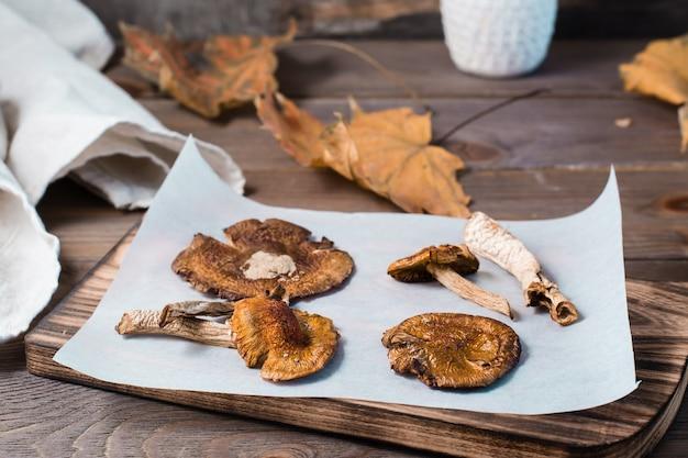 Suszone muchomory na pergaminie na drewnianym stole. mikrodozowanie i medycyna alternatywna. zbliżenie