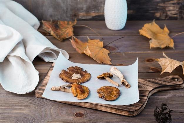 Suszone muchomory na pergaminie na drewnianym stole. mikrodozowanie i medycyna alternatywna.