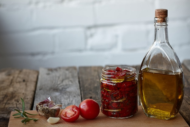 Suszone na słońcu pomidory z prowansalskimi ziołami, czosnkiem i oliwą z oliwek na rustykalnej drewnianej powierzchni