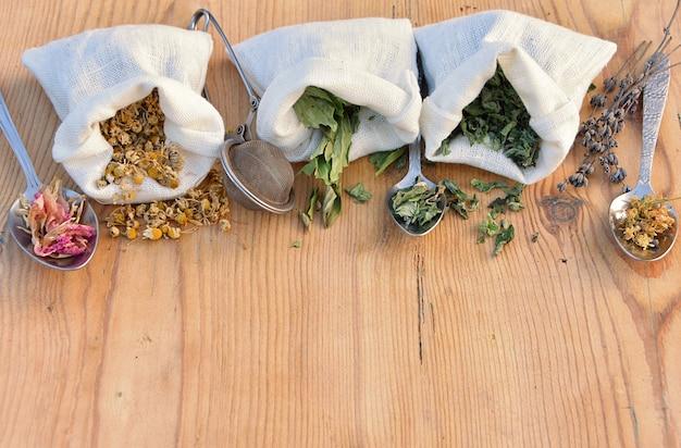 Suszone naturalne zioła w lnianych torebkach i łyżkach do herbaty ziołowej i lekarstw, medycyny alternatywnej, apteki domowej.