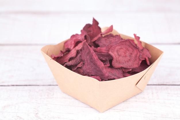 Suszone odwodnione chipsy buraczane w misce rzemieślniczej. pyszna ekologiczna ekologiczna przekąska dla całej rodziny. koncepcja zdrowego odżywiania.