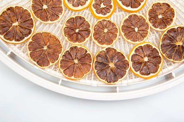 Suszone owoce cytrusowe w plastrach na plastikowej tacy do suszenia