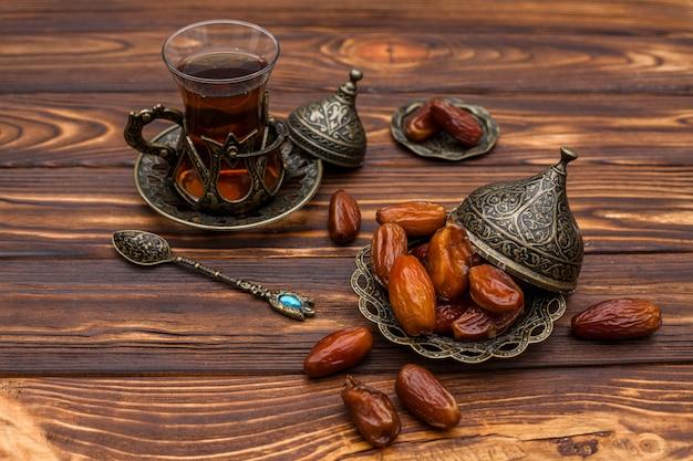 Suszone owoce daty na małym talerzu ze szklanką herbaty