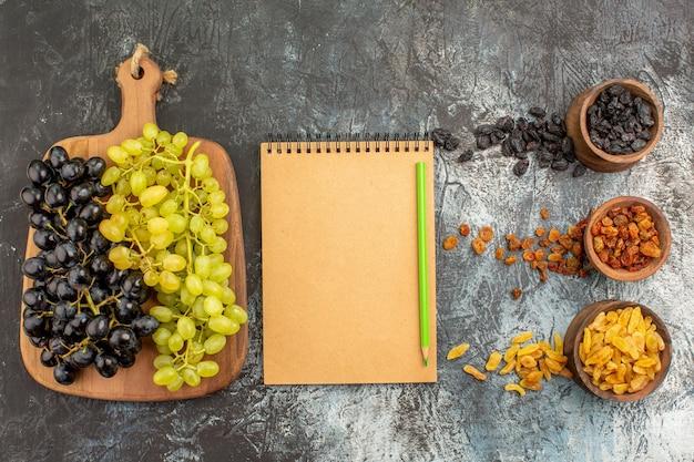 Suszone owoce deska zielonych i czarnych winogron ołówek zeszyt suszone owoce
