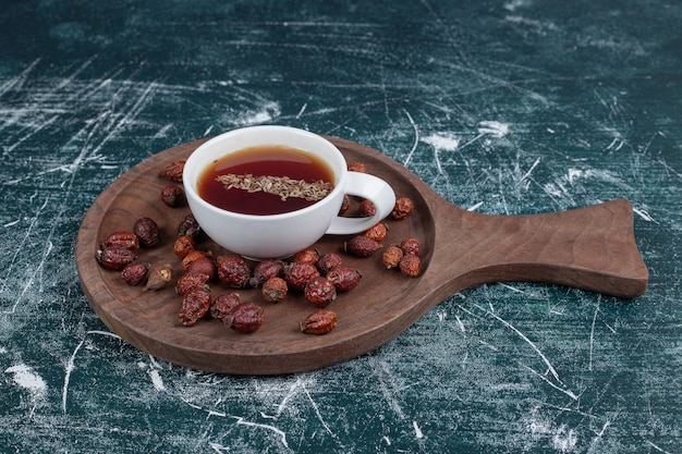 Suszone owoce dzikiej róży i filiżankę herbaty na desce. wysokiej jakości zdjęcie