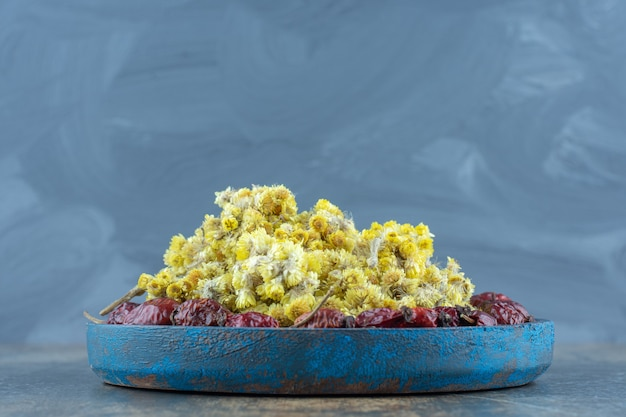 Suszone owoce dzikiej róży i kwiaty na niebieskim talerzu.