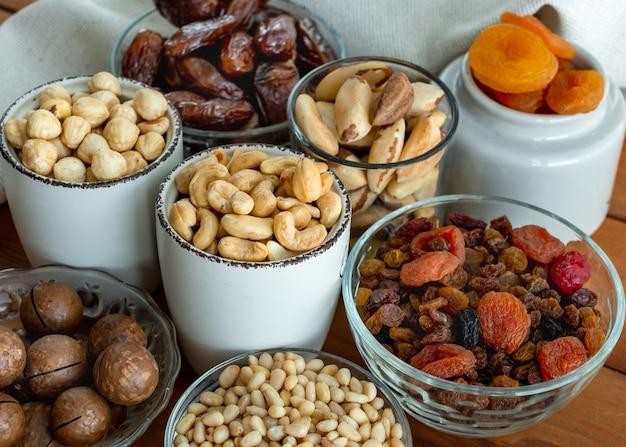 Suszone owoce i orzechy z bliska. selektywna ostrość. ekologiczne i zdrowe. trail mix migdałów, makadamii, sosny, orzechów brazylijskich, orzechów laskowych, daktyli, suszonych moreli