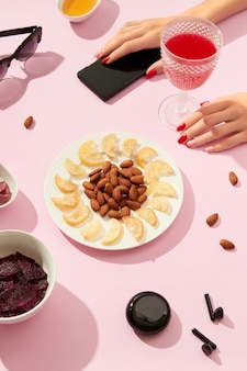 Suszone owoce i orzechy z sosem na różowym tle rękami womans