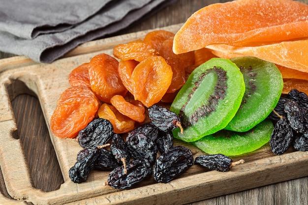 Suszone owoce i serwetki. stara deska kuchenna i drewniany stół.