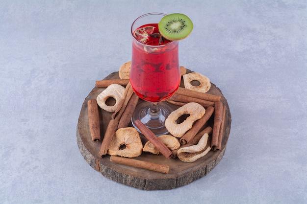 Suszone owoce, laska cynamonu i sok wiśniowy na desce, na marmurowym stole.