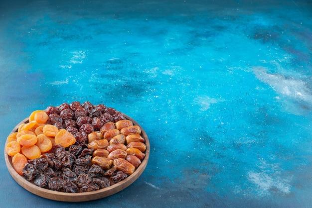 Suszone owoce na desce na niebieskiej powierzchni