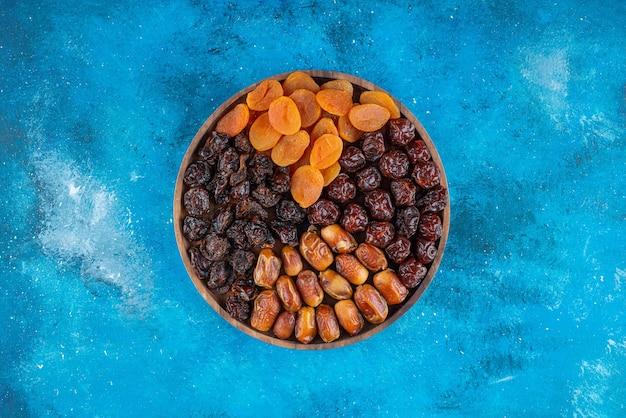 Suszone owoce na desce, na niebieskim stole.
