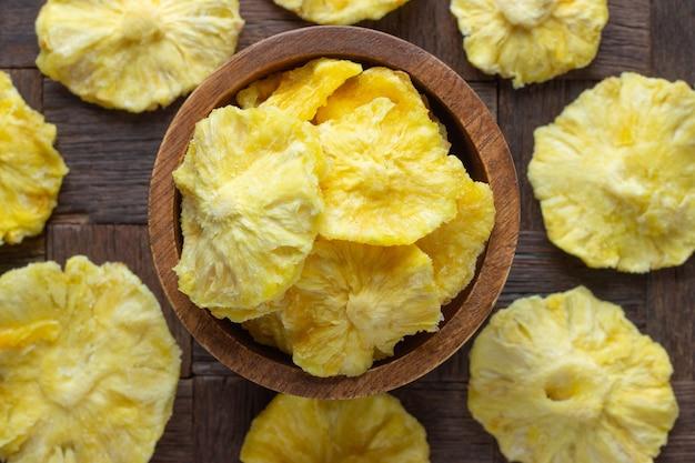 Suszone owoce, pierścienie ananasa w drewnianej misce, widok z góry.
