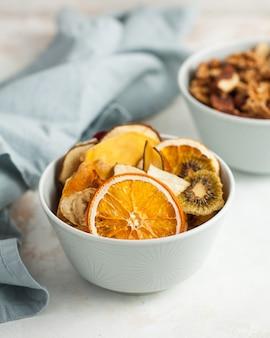 Suszone owoce pomarańcza, banan, kiwi, gruszka, mango, truskawki w niebieskim misce z bliska na jasnym tle z niebieską serwetką tekstylną