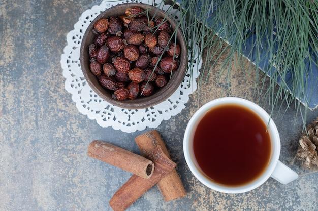 Suszone owoce róży, filiżanka herbaty i cynamon na marmurowej powierzchni. wysokiej jakości zdjęcie
