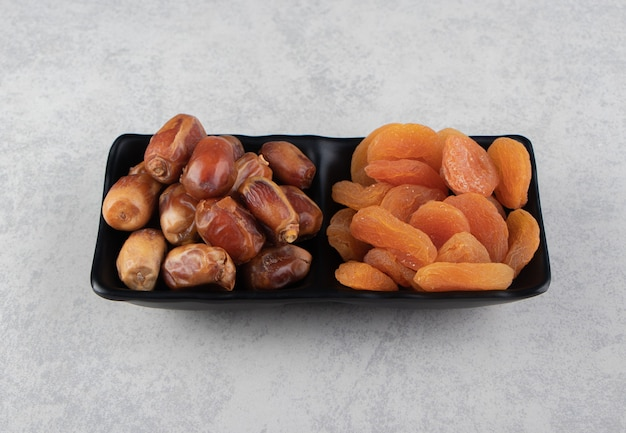 Suszone owoce w misce na marmurowej powierzchni