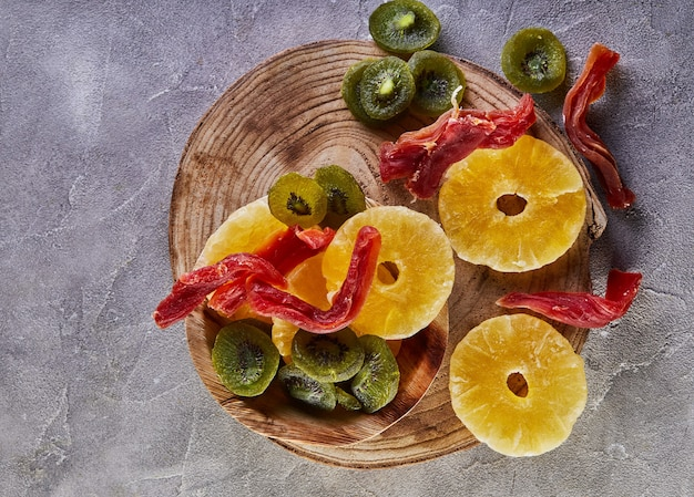 Suszone owoce: żółte kandyzowane krążki ananasa, czerwona papaja i zielone kiwi na drewnianej desce