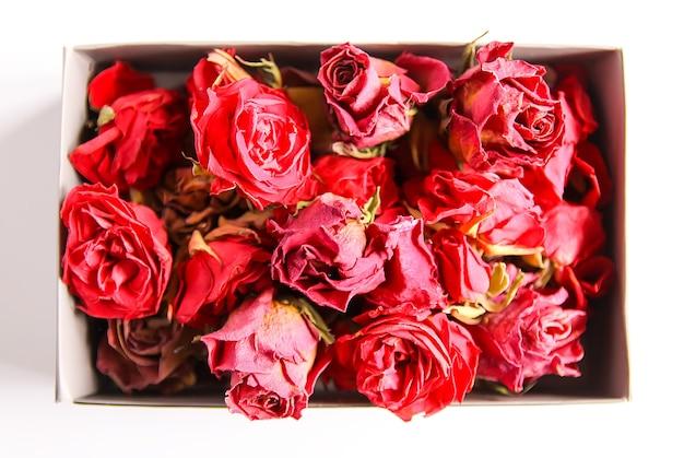Suszone pąki, kwiaty i płatki czerwonej róży w otwartym kartonie
