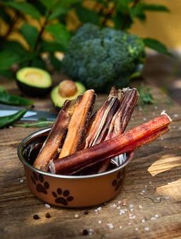 Suszone penisy wołowe w naczyniu psa na desce oraz niektóre noże i warzywa na tle. przysmaki do żucia dla psów domowych.