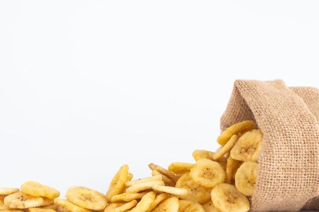 Suszone plasterki banana w worku worek spada z miejsca na kopię na białym tle