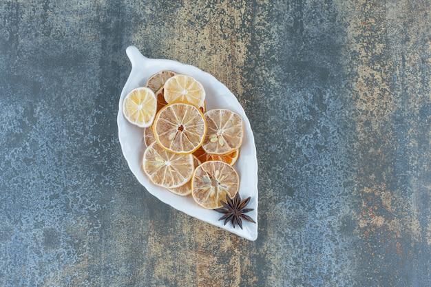 Suszone plasterki cytryny na talerzu w kształcie liścia.
