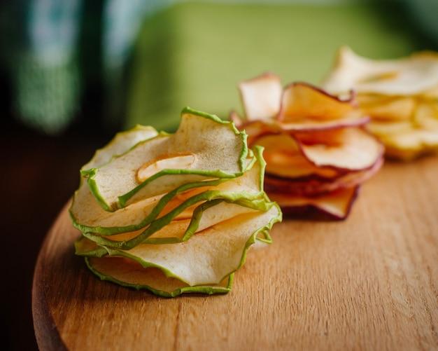Suszone plasterki jabłka w opakowaniu z papieru rzemieślniczego na powierzchni drewnianej. selektywna ostrość.