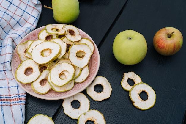 Suszone plasterki jabłka w otwartym szklanym słoju. domowe organiczne suszone chipsy jabłkowe ze świeżym jabłkiem na czarnym tle tabeli. słodka wegańska przekąska. pojęcie zdrowego i odżywiania. niewielka głębokość pola.