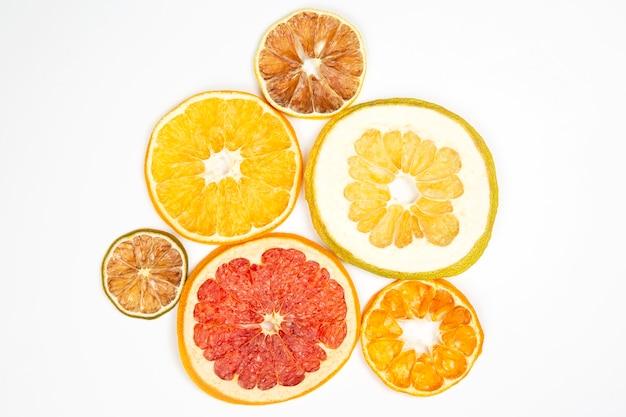 Suszone plasterki różnych owoców cytrusowych na białym tle