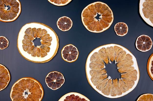 Suszone plasterki różnych owoców cytrusowych na czarnej drewnianej desce, widok z góry