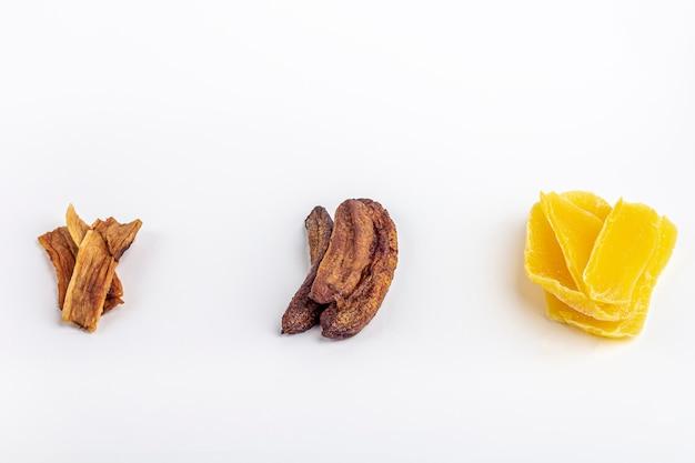 Suszone plastry mango, bananów i melona. organiczne chipsy z suchych owoców w papierowym ekologicznym opakowaniu na białym tle. zdrowa wegańska przekąska. koncepcja właściwego żywienia, żywności ekologicznej i wegetariańskiej, miejsce