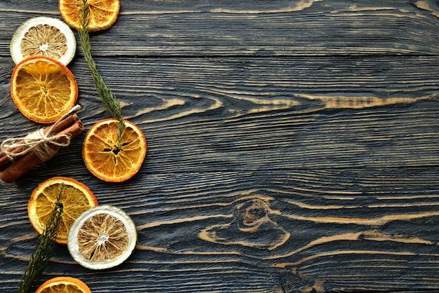 Suszone plastry pomarańczy i cynamonu na ciemnym drewnianym widok z góry.