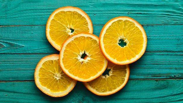 Suszone plastry pomarańczy na turkusowym tle drewniane. widok z góry.