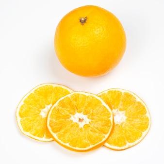 Suszone plastry pomarańczy obok świeżej pomarańczy na białej powierzchni
