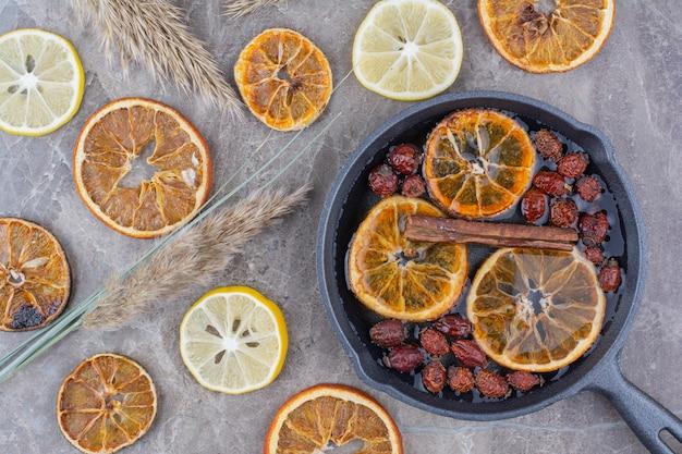 Suszone plastry pomarańczy, owoce dzikiej róży i cynamon na czarnej patelni.