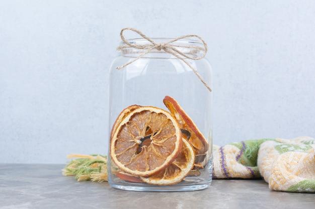 Suszone plastry pomarańczy w szklanym słoju na kamiennym stole.