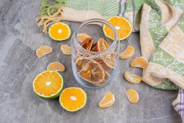 Suszone plastry pomarańczy w szklanym słoju na powierzchni kamienia.