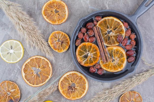 Suszone plastry pomarańczy z owocami dzikiej róży na czarnej patelni.