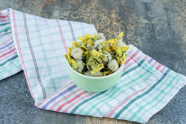 Suszone płatki chryzantemy w zielonej misce z obrusem.