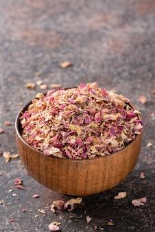 Suszone płatki róży herbaty w drewnianej misce