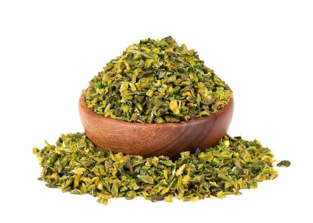 Suszone płatki zielonej papryki z nasionami w drewnianej misce, na białym tle. posiekane jalapeno, habanero lub papryczka chilli. przyprawy i zioła.