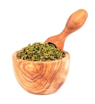 Suszone płatki zielonej papryki z nasionami w oliwnej misce i szufelką, na białym tle. posiekane jalapeno, habanero lub papryczka chilli. przyprawy i zioła.