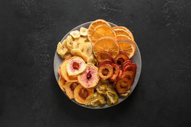 Suszone pokrojone śliwki kiwi owoce brzoskwini chipsy na czarno