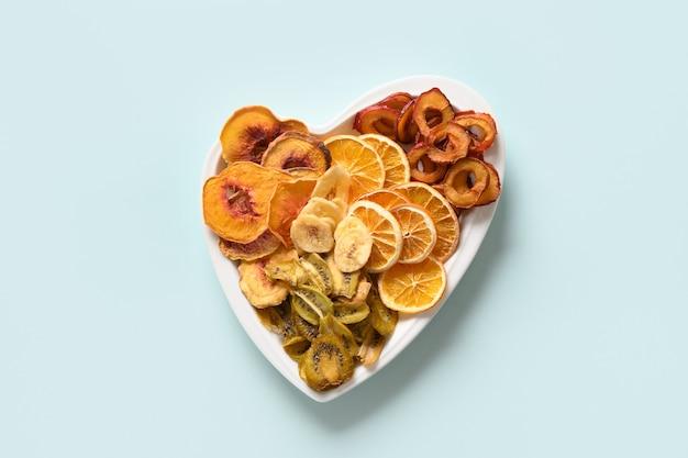 Suszone pokrojone śliwki kiwi owoce brzoskwini chipsy na niebiesko