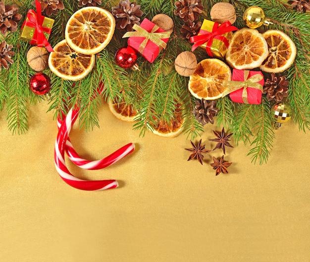 Suszone pomarańcze i szyszki ozdoby świąteczne i gałązka spruse na złotym tle