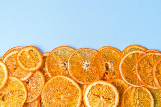 Suszone pomarańczowe chipsy owocowe na niebiesko z copyspace.