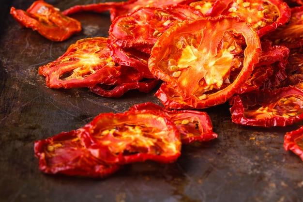 Suszone pomidory na ciemnej powierzchni rustykalnej