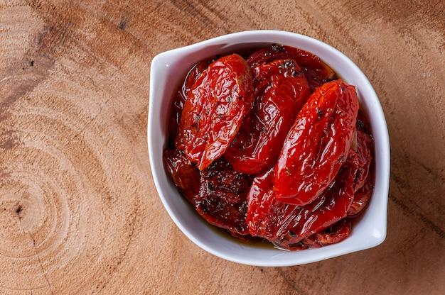 Suszone pomidory w białej misce na drzewnym tle