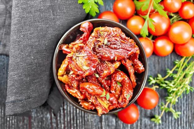 Suszone pomidory w oleju z tymiankiem i bazylią w misce, serwetka, świeże małe pomidory i pietruszka na tle drewnianej deski z góry