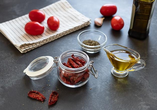 Suszone pomidory w szklanym słoiku, przyprawy i oliwa z oliwek na ciemnym stole w kuchni. przekąska antipasti