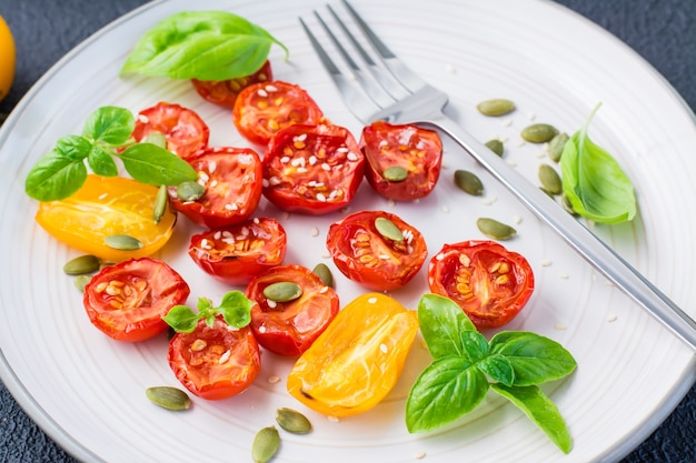 Suszone pomidory z bazylią, sezamem i dynią na talerzu na czarnym tle. jedzenie wegetariańskie. zbliżenie
